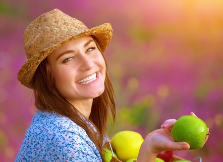 Closeup portrait of happy beautiful female offers an apple, laughing in floral garden, bright sunset light, farming and harvesting concept photo