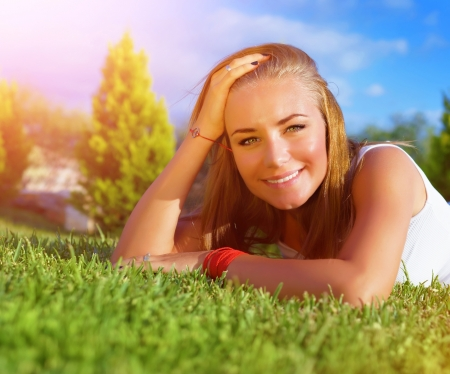 Closeup portrait of cute woman lying down on green grass field, relaxation outdoors, summer holidays, carefree lifestyle, vacation concept photo