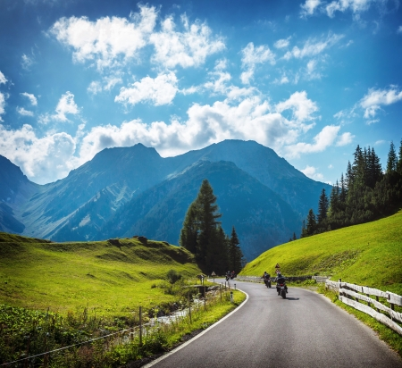 Group of motorbikers in the mountains, race on mountainous highway, beautiful landscape, trip along Alps, travel and tourism concept