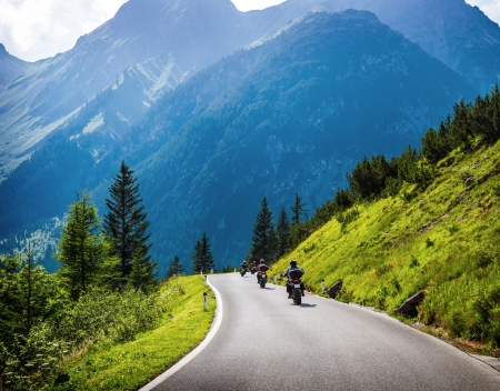 Moto racers riding on mountainous road, drive a motorcycle, summer adventure, extreme sport, travel to Europe, active lifestyle, vacation concept  photo