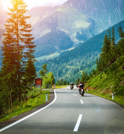 Group of bikers in Alps, active vacation, curve road in the mountains, fresh pine trees along highway, bright sunshine, extreme transportation