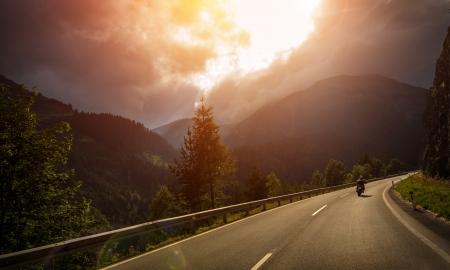 motociclista: Motorista en la acción, brillante luz roja puesta de sol, el clima nublado, estilo de vida activo, viajando a lo largo de las montañas alpinas, el concepto de aventura extrema Foto de archivo