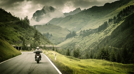 adventure holiday: Motorcyclist on mountainous highway, cold overcast weather, Europe, Austria, Alps, extreme sport, active lifestyle, adventure touring concept