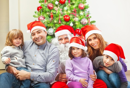 large family portrait: Large family and Santa Claus sitting near Christmas tree at home, wearing red festive hat, winter holidays, New Year celebration