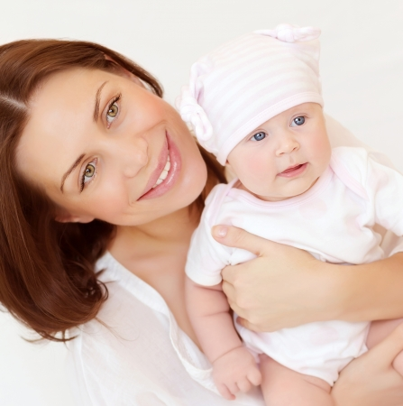 Closeup portrait of beautiful young mother carry little baby, at home, healthy childhood, child's safety concept photo