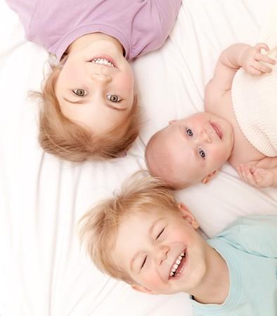 Close-up portret van drie vrolijke kinderen liggen thuis, pasgeboren baby met broer en zus, gelukkige familie, liefde en vriendschap begrip Stockfoto - 22349641