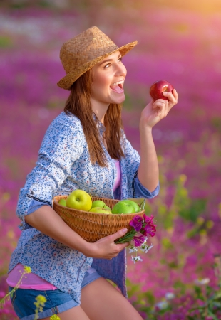 Cute girl biting red apple, young farmer enjoying harvest, relaxation in beautiful floral garden, eating fruits, healthy lifestyle concept  photo
