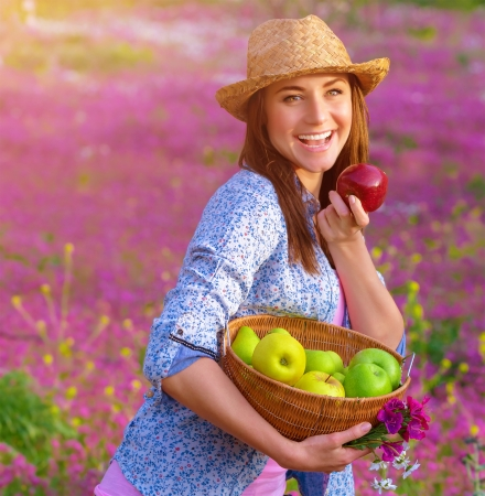 Closeup on nice cheerful woman wearing straw hat biting apple, sunset light, pink floral glade, countryside, autumnal harvest season photo
