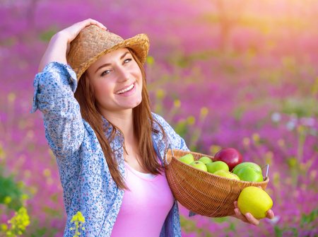 Closeup portrait of pretty woman with apples basket, having picnic on pink floral meadow, harvest season, gardening concept photo