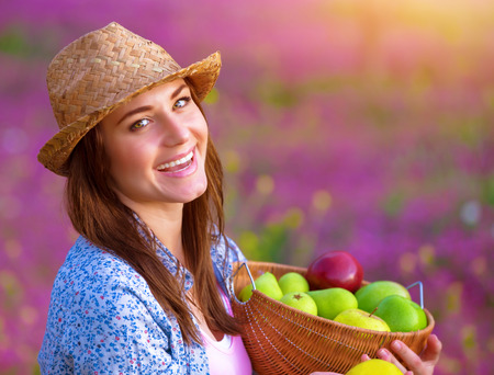 Closeup portrait of cute cheerful female with fresh apple basket in the garden, enjoying fruits, sunny day, harvest season, eating vitamins concept photo