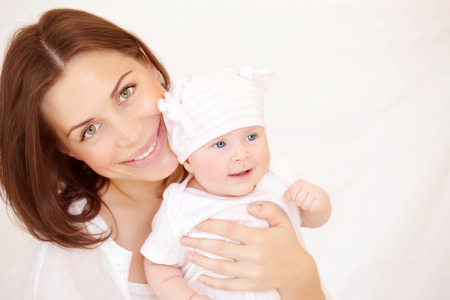 Closeup portrait of beautiful young mother carry cute little baby girl, at home, healthy childhood, new life concept photo