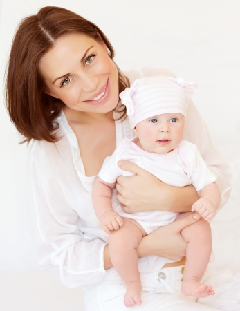 Portrait of attractive brunette mother carry cute baby girl in hands, at home, happy motherhood, young family, love concept photo