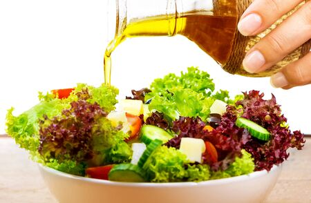 cutting vegetables: Fresh salad with olive oil isolated on white background, pouring salad dressing into cutting vegetables, organic food, healthy nutrition concept
