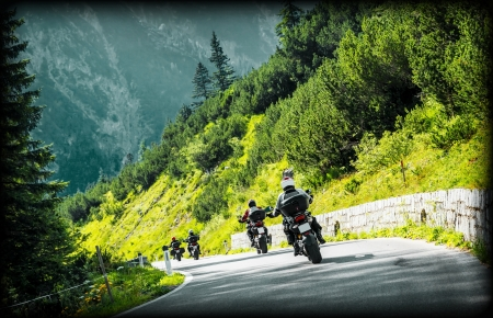 motorbikes: Group of moto bikers on mountainous highway, riding on curve road pass across Alpine mountains, extreme lifestyle, freedom concept