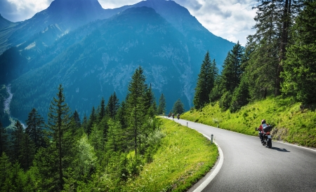Motorcyclists in mountainous touring, extreme adventure, European journey, extreme road along Alps, active holiday concept Stock Photo