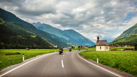 Bikers on mountainous highway, Europe, Austria, Alps, road along little village, driving motorcycle, extreme sport, active lifestyle concept photo