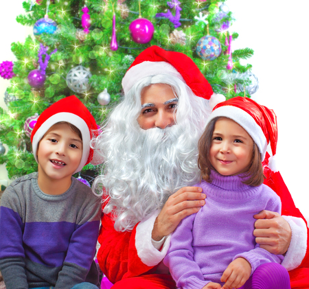 Portrait of two adorable kids sitting with Santa Claus at home near Christmas tree, winter holidays, New Year party, festive decorations, fun concept photo