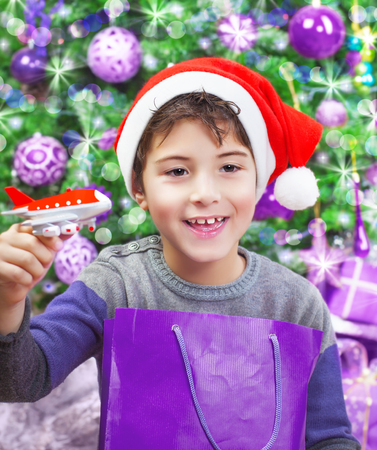 Portrait of cute arabic boy enjoying Christmastime gift, playing with little plastic airplane, wearing red Santa hat, decorated Christmas tree, New Year eve photo