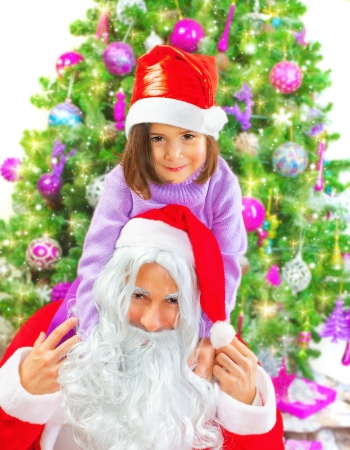 Portrait of Santa Claus holding on back cute little girl, beautiful decorated Christmas tree, New Year childs party, winter holidays concept photo