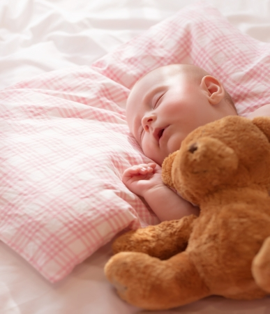Little baby asleep with plush bear toy, newborn girl napping in the bed at home, child care, closed eyes, healthy lifestyle, happy childhood concept photo