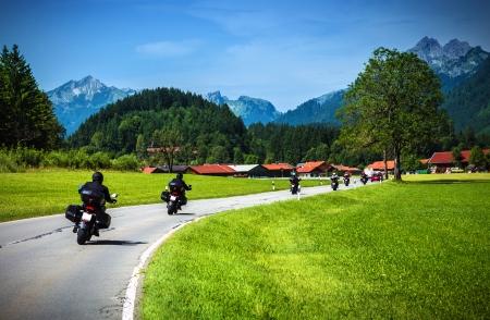 Bikers on mountainous road, touring across Alpine mountains, along little village, beautiful landscape, travel and tourism concept
