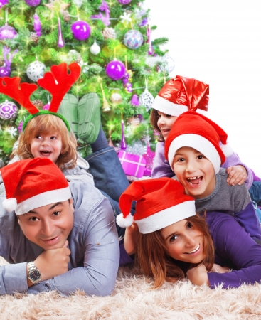 Portrait of happy large family celebrating Christmas holidays at home, lying down near Xmas tree, wearing red Santa hat, New Year eve photo