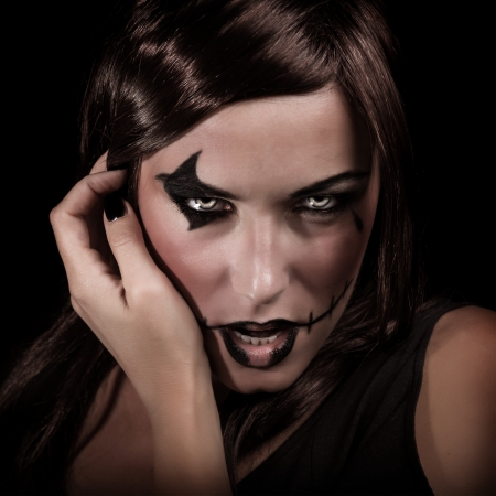 terrifying: Scary portrait of young woman with aggressive makeup isolated on black background, terrifying witch, spooky vampire, Halloween party concept
