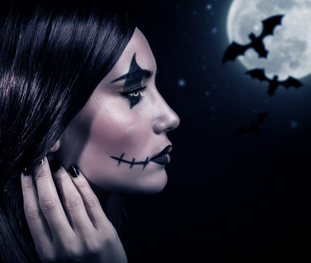 terrifying: Side view of terrifying witch in Halloween night, bats on full moon background, portrait of werewolf on scary dark night, horror concept Stock Photo