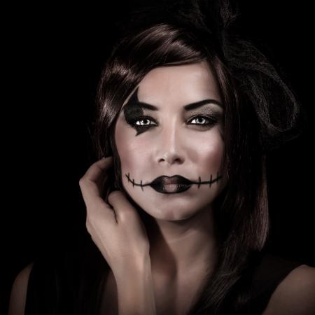 harridan: Primer retrato de mujer joven con maquillaje miedo aislados en negro, traje del carnaval de la bruja, concepto de fiesta de Halloween