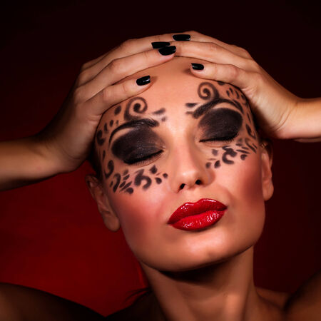 Closeup portrait of sexy seductive female with closed eyes and luxury makeup isolated on dark red , Halloween party  photo
