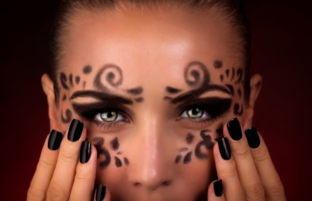 faceart: Closeup portrait of beautiful woman with perfect festive makeup on dark background, face part, masquerade face-art, Halloween party concept