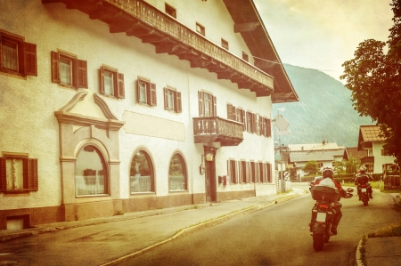 touring: Bikers in European city, beautiful retro style photo, grunge image, spending vacation on mountains, extreme adventure, active touring concept Stock Photo