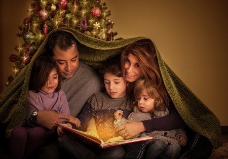 stories: Big family reading interesting magic story in Xmas eve, happy parents with cheerful children covered with blanket, Christmas tree at home, New Year celebration