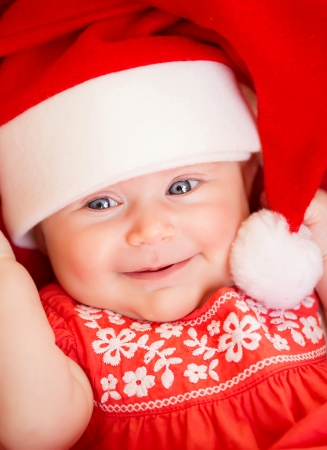 Closeup portrait of beautiful newborn baby wearing red Santa Claus hat, Christmas party, New Year celebration, happiness concept photo