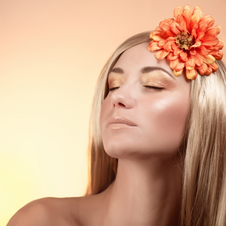 Closeup portrait of attractive female with long glossy blond hair and autumnal flower in head isolated on beige background, fashionable golden makeup Stock Photo - 22936551