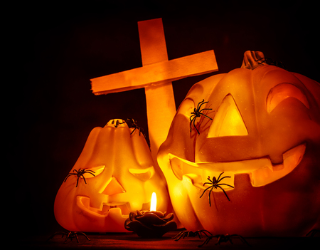 antichrist: Closeup on glowing carved pumpkin with creepy spiders on graveyard, mysterious cross on dark Halloween night