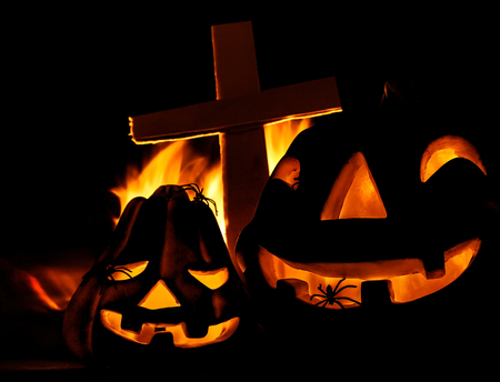 Scary glowing pumpkin decoration with creepy spider, burning fire, cross on the cemetery, Halloween fun, misterious holiday celebration photo