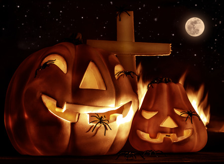 Creepy Halloween night, glowing carved pumpkin with scary horrible spiders, cross and burning flame on the graveyard in full moon night
