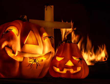 carved pumpkin: Scary Halloween night, aggresive burning fire on cemetery near cross, terrible carved pumpkin face laughing, holiday party, horror concept