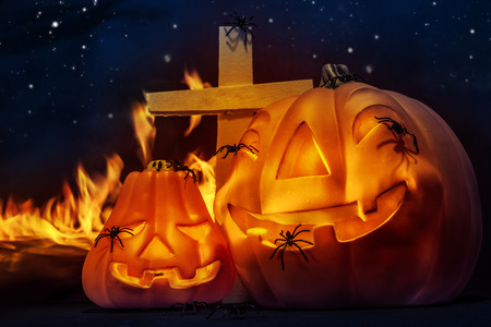Creepy Halloween night, glowing carved pumpkin with scary horrible spiders, cross and burning flame on the graveyard in mysterious dark night photo
