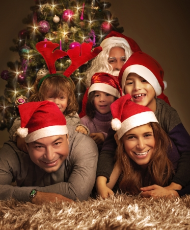 christmas night: Closeup portrait of big happy family with Santa Claus lying down near Christmas tree, holiday celebration, joy and happiness concept