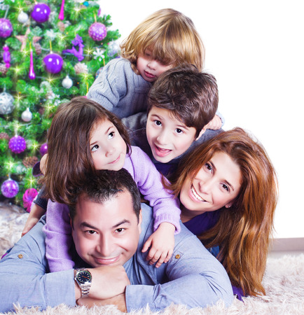 Cheerful large family having fun at home near Christmas tree, winter holidays, New Year celebration, parents with kids enjoying Christmastime photo