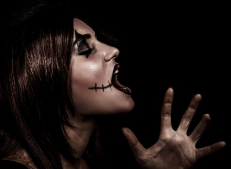 beldam: Scary witch yelling, side view of aggresive woman with painted face on black background, terrible grimace, Halloween party concept