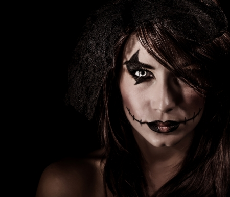 Terrifying witch portrait isolated on black background, attractive woman with scary makeup, Halloween party, horror concept photo