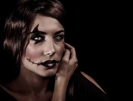 Closeup portrait of beautiful female with aggresive makeup for Halloween party, scary autumnal party celebration, mystery concept photo
