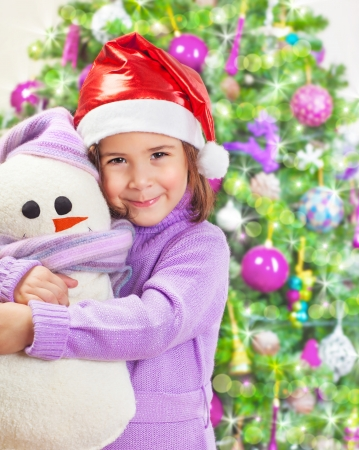 Beautiful little happy girl wearing red Santa hat and holding in hands snowman soft toy, Christmas tree, happy winter holidays photo
