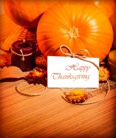 Thanksgiving day still life on wooden table, autumnal holiday, ripe orange gourd with candle and dry flowers, greeting card, harvest season concept  photo