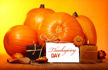 Thanksgiving day decoration for holiday celebration, pumpkin with greeting card on wooden table on yellow background, autumn season concept photo