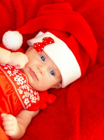 Portrait of cute baby girl wearing red Santa Claus hat with bow lying down in the bed at home, New Year party for children photo