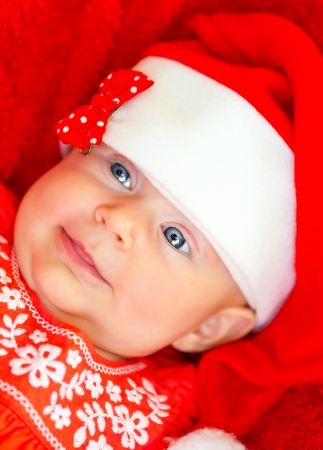 Closeup portrait of sweet little baby girl wearing red festive dress and Santa hat, having fun on Christmas party, wintertime holidays photo